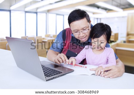 Lovely female elementary school student studying with male teacher in the classroom, using a book and laptop on the table