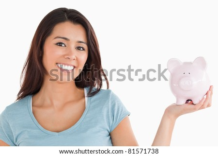Lovely female holding a piggy bank while standing against a white background