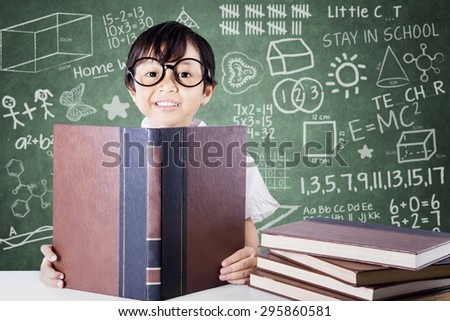 Lovely female primary school student wearing glasses and reading textbooks in the classroom - stock photo