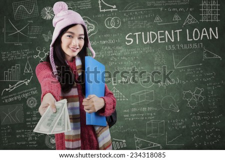 Lovely female student wearing warm clothes in the class and giving money dollars  - stock photo