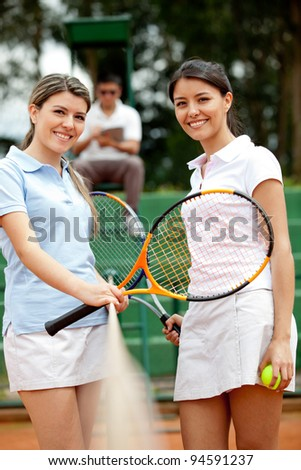 Lovely female tennis players at the court smiling