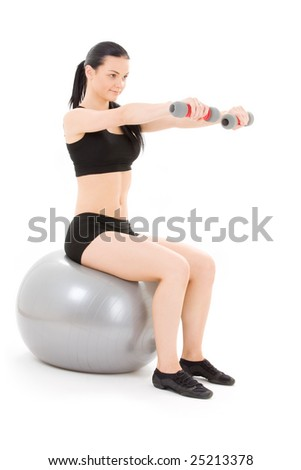 lovely fitness instructor with dumbbells on pilates ball