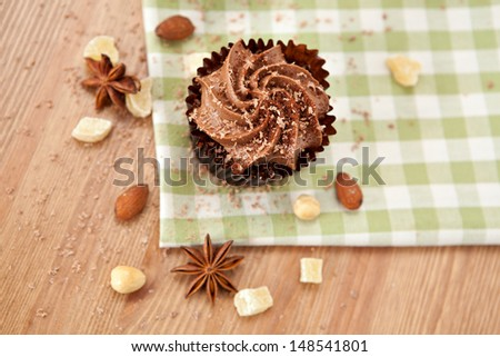 Lovely fresh chocolate cupcake on green cloth. Very shallow depth of field  - stock photo
