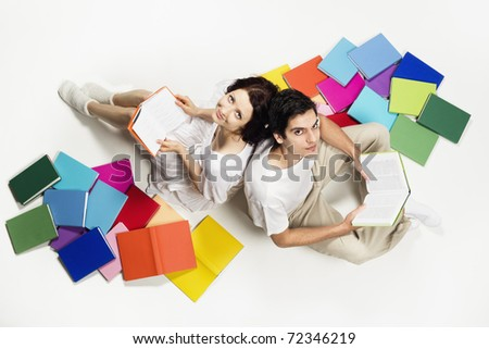 Lovely girl and boy sitting on floor with colorful books and reading, looking up, isolated on white background. - stock photo