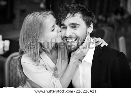 Lovely girl embracing and kissing her boyfriend - stock photo