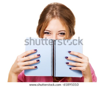 Lovely girl hiding behind notebook, white background - stock photo