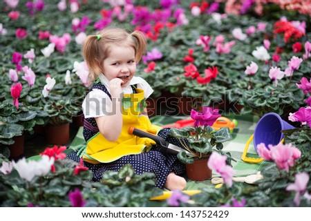 Lovely girl holding flowers in garden center. - stock photo