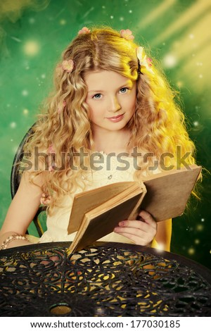 Lovely girl in a lush white dress sitting at the table  over green background and reading a book.  - stock photo