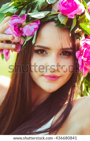 lovely girl in colored wreath looks in a camera