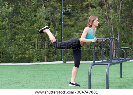 Lovely girl in sportswear on the playground doing fitness. - stock photo