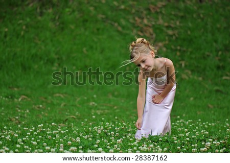 Lovely girl is posing on the grass - stock photo