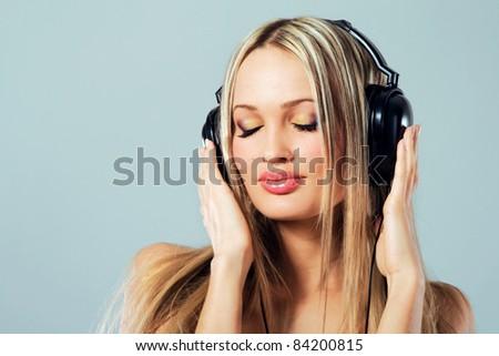 Lovely girl listening a music in headphones - stock photo