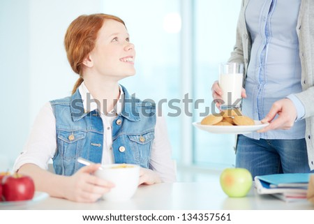 Lovely girl looking at her mother while she offering her milk and bisquits - stock photo