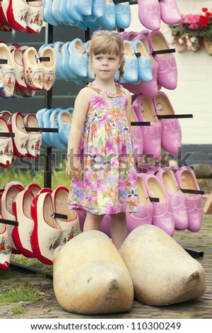 Lovely girl posing in typical dutch huge wooden clogs - stock photo
