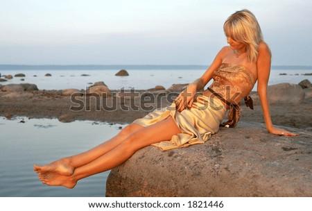 lovely girl relaxing on the rock - stock photo