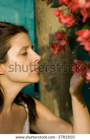 lovely girl smelling red flowers