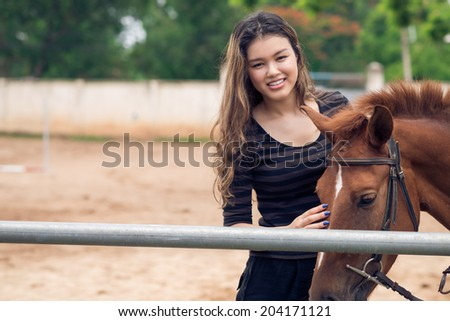 Lovely girl stroking her horse - stock photo
