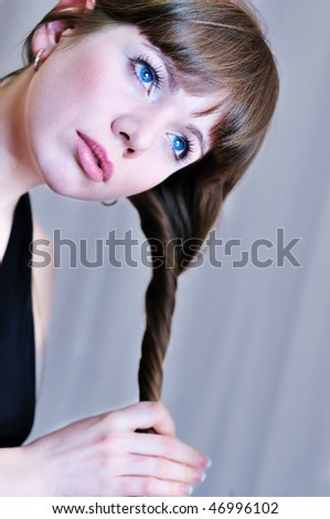 lovely girl  twisting her long hair over the gray - stock photo