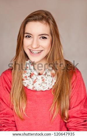Lovely girl wearing braces smiling joyfully - stock photo