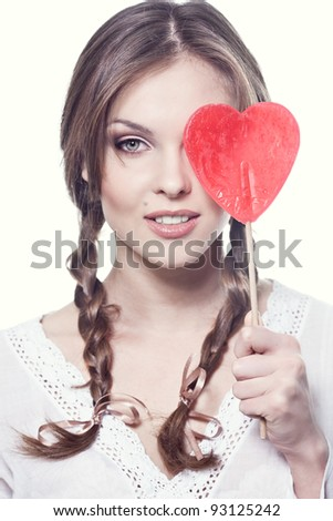 Lovely girl with a heart-shaped candy - stock photo