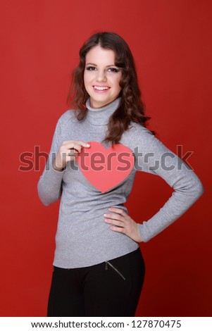 Lovely girl with charming smile/Brunette woman with heart symbol on Holiday theme - stock photo