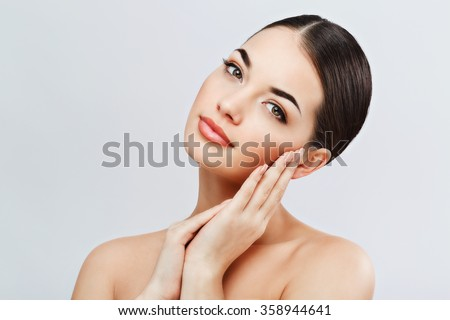 Lovely girl with dark hair and dark eyebrows, with naked shoulders, touching face and looking at camera, a model with light nude make-up, gray studio background, beauty photo, copy space.  - stock photo