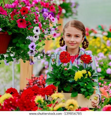Lovely girl with flowers in garden center. - stock photo
