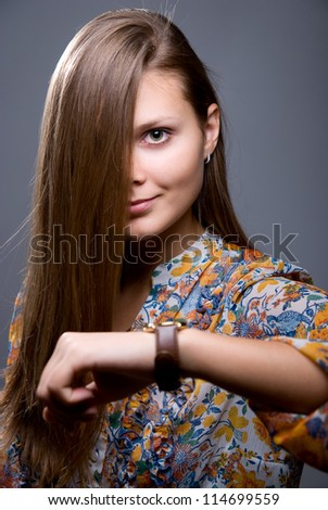 Lovely girl with long hair.Looking at the picture - stock photo