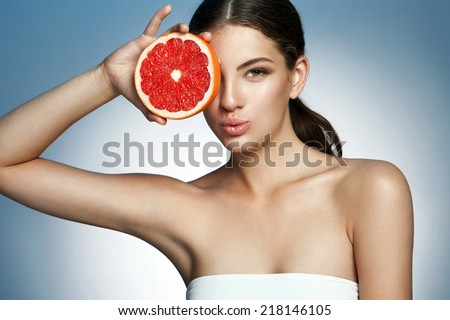 Lovely girl with pomelo slice, natural organic raw fresh food concept / photoset of attractive girl holding a cut piece of Sicilian orange on blue background  - stock photo
