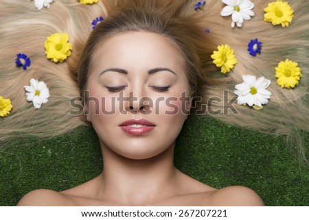 lovely girl with relaxed expression and perfect skin posing in close-up beauty portrait lying on garden with some colourful flowers in her long and smooth  hair  - stock photo