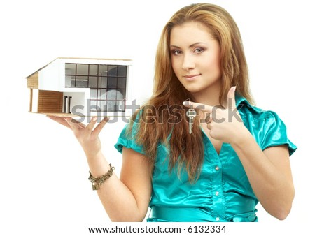 lovely girl with small house in hand and key on finger - stock photo