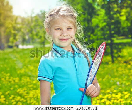 Lovely girl with tennis racket looking at camera in park - stock photo
