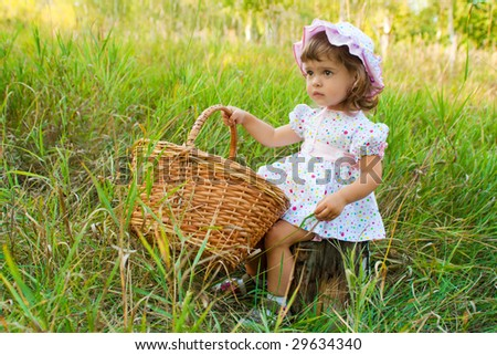 Lovely girl with wicker basket in a wood