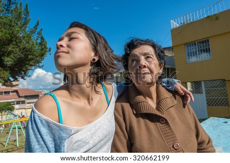 Lovely grandmother and granddaughter sitting together enjoying quality time outdoors. - stock photo