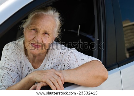 Lovely grandmother in the car - stock photo