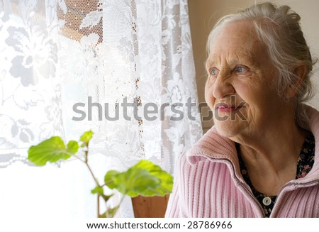 Lovely grandmother looking in the window - stock photo