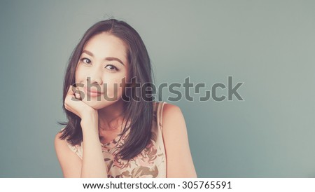 Lovely hand on chin pose. Vintage, retro style of portrait of Asian woman in pink vintage dress on blue and green background. - stock photo
