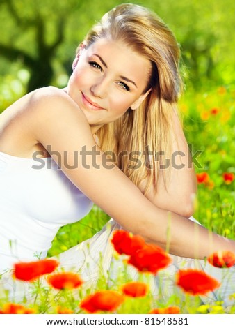 Lovely happy female closeup portrait, sitting in the poppy flower field, enjoying nature, summertime leisure concept - stock photo