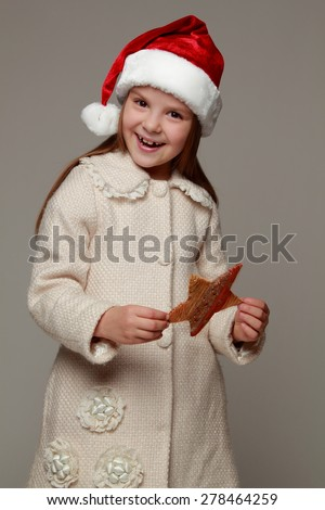 Lovely happy little girl with long hair in Santa hat holding christmas star isolated on white/Christmas portrait of a cute child in a Santa's hat - stock photo