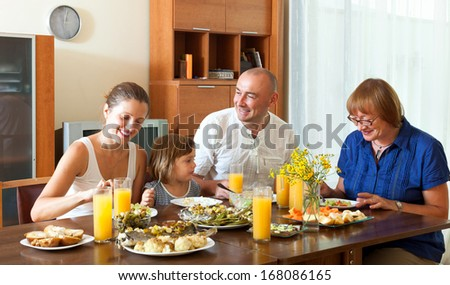 Lovely happy multigeneration family having healthy dinner at home together - stock photo