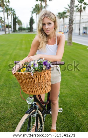 Lovely hipster girl looks at camera while standing in the park on a green lawn with her classic bicycle with basket of beautiful flowers, attractive young woman enjoying leisure during summer vacation - stock photo