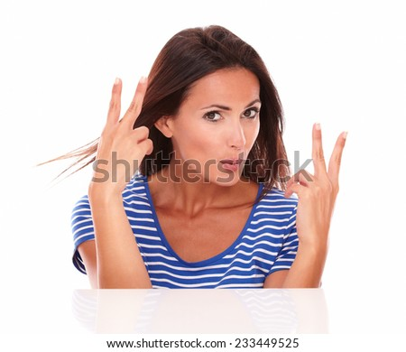 Lovely hispanic making a victory sign and feeling a winner while looking at camera in white background
