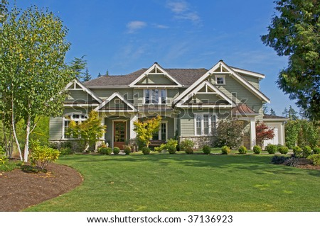 lovely house with lush green grass & blue sky - stock photo