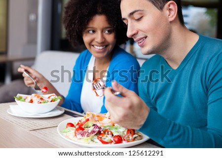 Lovely interracial couple having lunch at restaurant - stock photo