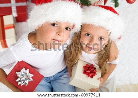 Lovely kids at christmas time with santa hats and presents - stock photo