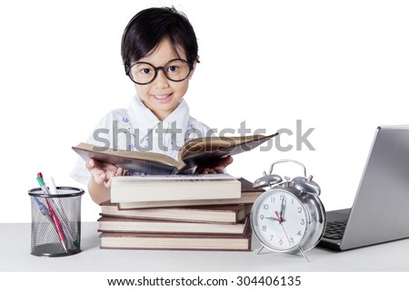 Lovely kindergarten student reading books on the table while wearing glasses and smiling at the camera - stock photo