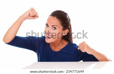 Lovely lady in blue shirt gesturing winning while looking at you in white background - stock photo