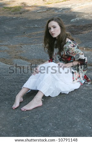 Lovely lady sitting on a stone