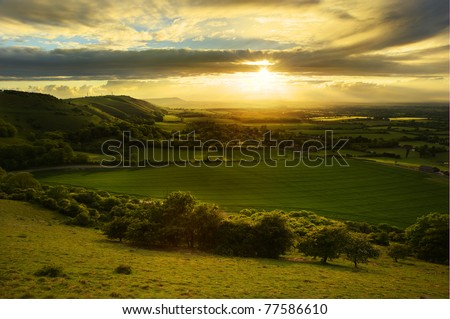 Lovely landscape of countryside hills and valleys with setting sun lighting up side of hills whit sun beams through dramatic clouds - stock photo