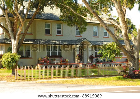 Lovely landscaped, two story home with columns, brick on widow sills and porch. A wood slat fence offers a barrier but does not impede it's warmth and inviting view. - stock photo